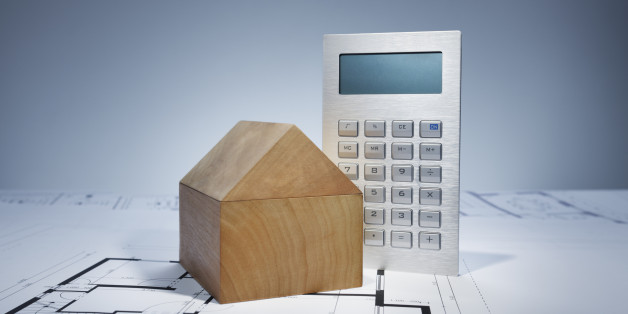 Blueprint with wooden house and calculator