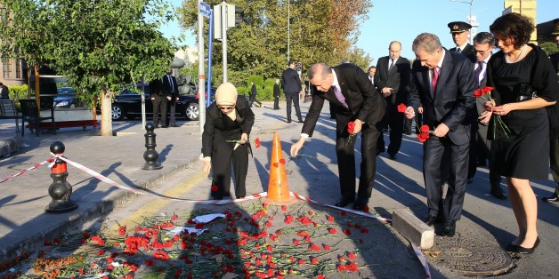 ANKARA, TURKEY - OCTOBER 14: Turkish President Recep Tayyip Erdogan (L-2), his wife Emine Erdogan (L), Finnish President Sauli Niinisto (R-2) and and his wife Jenni Haukio (R) lay red carnations at the site of twin bombings to pay tribute to the victims of the attacks near Ankara train station on October 14, 2015 in Ankara, Turkey. Two suicide bombers, using five kilograms of TNT explosives each, carried out Saturday's twin bomb blasts in Ankara that killed at least 97 people, Turkish Deputy Prime Minister Numan Kurtulmus said late Monday. (Photo by Kayhan Ozer/Anadolu Agency/Getty Images)
