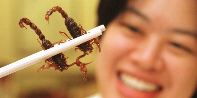 """--Singaporean diner Sum June-wei holds two scorpions between her chopsticks at the Imperial Herbal Restaurant in Singapore Jan. 25, 1996.  The scorpions, imported from China, cost $4 each in a dish called """"deep-fried drunken scorpion with asparagus."""" Customers are told that the scorpion's poison soothes nerves and cures migraine. (AP Photo/Mike Fiala)"""