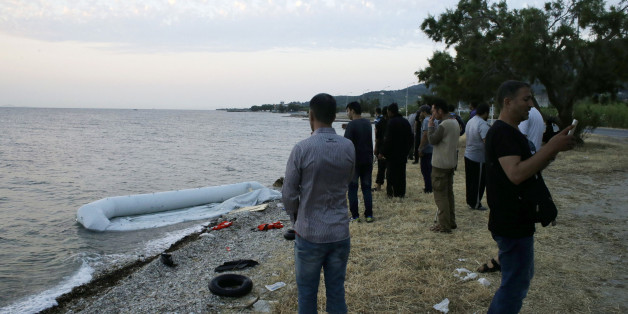 Syrian migrants gather next to their destroyed dinghy after their arrival from Turkish coasts at a Mytilene beach, on the northeastern Greek island of Lesvos, early Thursday, June 18, 2015. Around 100,000 migrants have entered Europe so far this year, with some 2,000 dead or missing during their perilous quest to reach the continent. Italy and Greece have borne the brunt of the surge, with many more migrants expected to arrive from June through to September. (AP Photo/Thanassis Stavrakis)