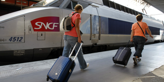 People walk on a platform to take a TGV (High Speed Train) at the Gare St-Charles station in Marseille, southern France , Thursday, June 12, 2014