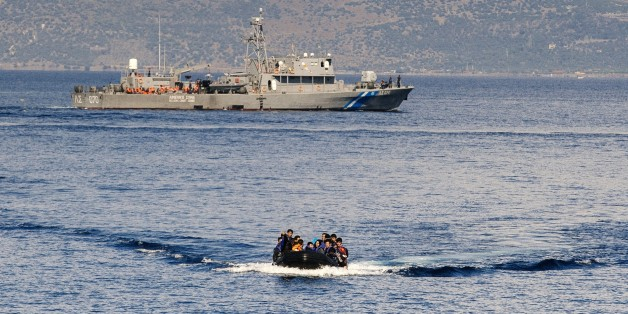 A Greek coast guard ship is seen behind a rubber boat with refugees and migrants near the Greek island of Lesbos after crossing the Aegean Sea from Turkey on October 13, 2015. Greece pledged On October 10, 2015 during talks with its EU partners to open its first so-called hotspot reception centre on the island of Lesbos within 10 days under EU efforts to better deal with the massive influx of migrants. AFP PHOTO / DIMITAR DILKOFF        (Photo credit should read DIMITAR DILKOFF/AFP/Getty Images)