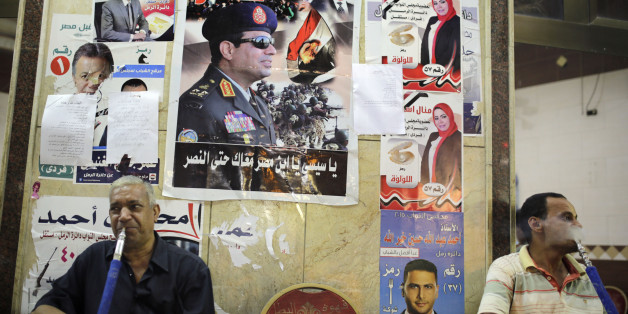 "Egyptians smoke traditional ""Shisha"", water pipe, under a poster of President Abdel-Fattah el-Sissi, centre, with Arabic that reads, ""Viva Egypt"", and posters with pictures of parliamentary candidates, ahead of parliamentary elections next week. (AP Photo/Amr Nabil)"