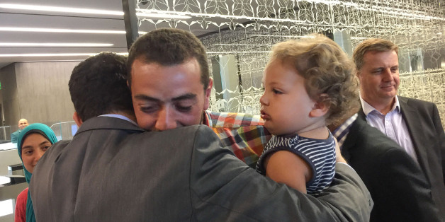 Egyptian Al-Jazeera English journalist Baher Mohammed, carrying his son Haroon, is welcomed by his colleagues upon his arrival to Doha, Qatar, Wednesday, Oct. 14, 2015. Baher and his Canadian colleague Mohamed Fahmy were among a group of 100 people pardoned by Egyptian President Abdel-Fattah el-Sissi on the eve of the major Muslim holiday of Eid al-Adha. (AP Photo)