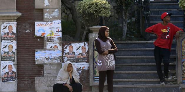Alexandrie, le samedi 17 octobre 2015, des  Egyptiens en attente de bus devant des affiches de candidats parlementaires (AP Photo/Hassan Ammar)