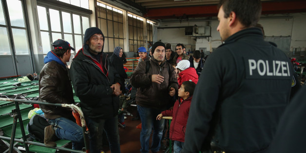 Flüchtlinge sprechen mit einem Polizisten in einem Erstaufnahmelager in Passau