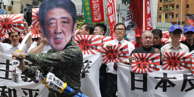 "An activist dressed as Japanese Prime Minister Shinzo Abe poses with Japanese military flags reading ""Japan must apologize"" during an anti-Japan protest outside of the Japan trade office in Taipei, Taiwan, Saturday, Aug. 15, 2015. In a statement marking the anniversary of Japan's surrender, Abe acknowledged Friday that Japan inflicted ""immeasurable damage and suffering"" on innocent people in World War II, but stopped short of offering his own apology and said future generations of Japanese shoul"