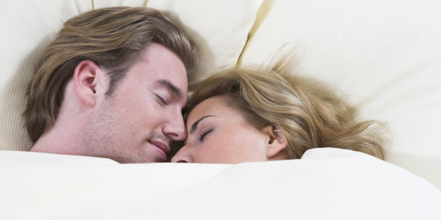 headshot of young couple sleeping closely together in bed