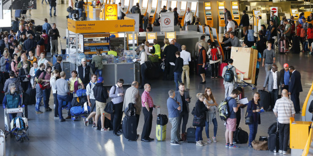 Passengers queue in front of the counters in a terminal at the airport as Lufthansa pilots went on a strike in Frankfurt, Germany, Wednesday, Sept. 9, 2015. The pilots ask for retirement arrangement under which pilots could retire at 55 and receive 60 percent of their salary until they reach the statutory retirement age of 65. (AP Photo/Michael Probst)