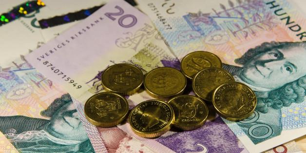 Swedish 10 SEK coins at partly unfocused banknotes
