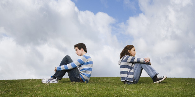 Teenage couple turned away from one another in field