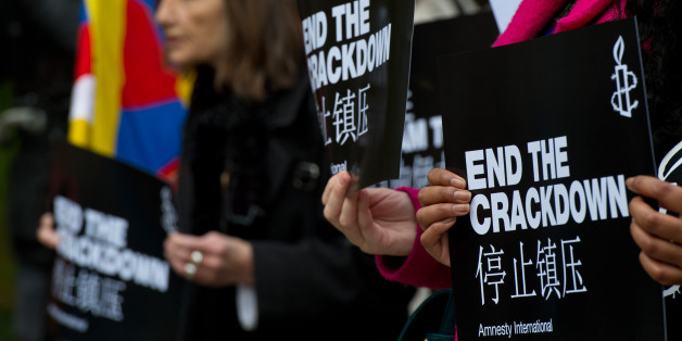 An Amnesty International supporter holds a sign with the slogan 'end the crackdown' in protest against claims of a deterioration in human rights and censorship of the internet and media during a state visit by Chinese President Xi Jinping