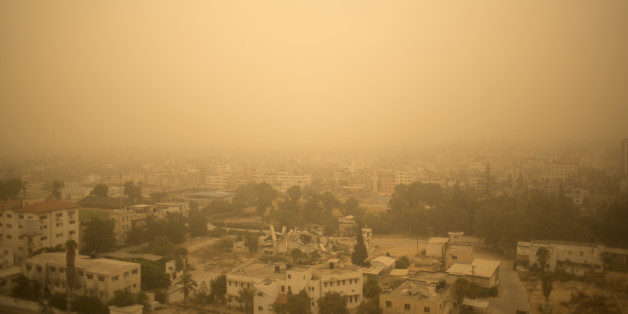 A sandstorm shrouds the Gaza strip, Tuesday, Sept. 8, 2015. An unseasonal sandstorm hit many countries in the Middle East with a blanket of yellow dust on Tuesday, sending hundreds of people to hospitals with breathing difficulties and causing the deaths of two women, officials said. (AP Photo/ Khalil Hamra)