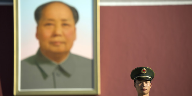 A Chinese guard stands on duty beneath the large portrait of former Chinese leader Mao Zedong on Tiananmen Gate after a flag raising ceremony on National Day, the 66th anniversary of the founding of the People's Republic of China, in Beijing, Thursday, Oct. 1, 2015. (AP Photo/Mark Schiefelbein)