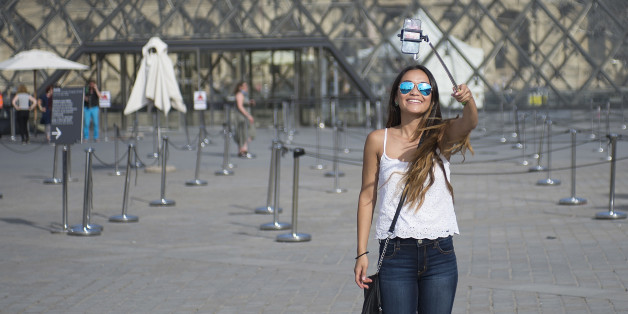 PARIS, FRANCE - AUGUST 06: A tourist takes a selfie using a selfie stick in front of the Louvre Pyramid on August 6, 2015 in Paris, France. Using a selfie stick has become a more and more common place among tourists but a number of high-profile attractions in Paris and other cities have started to ban them over fears of potential damage to exhibits. (Photo by Vanni Bassetti/Getty Images)