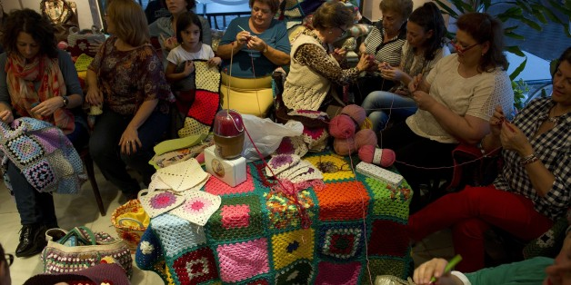 TO GO WITH AFP STORY BY DANIEL SILVA Women knit blankets for Syrian people, at 'La Cafeteria' cafe in Villaverde del Río in on October 15, 2015. At home alone or hudled together in groups in cafes, women of all ages across Spain have furiously knitted blankets to send to war-torn Syria before cold weather starts in response to an online appeal for help. Every night for the past week, a team of some 20 women and girls have met in a café in the heart of Villaverde del Rio, a town of white-washed houses near Seville, to finish their blankets and send them to a small NGO of Madrid, Syrian People Support Association.    AFP PHOTO/ CRISTINA QUICLER        (Photo credit should read CRISTINA QUICLER/AFP/Getty Images)