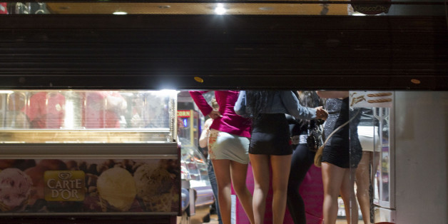 "Prostitutes hide from riot police inside of a store during the eviction of a few activists who gathered at Puerta del Sol square to mark the anniversary of the ""indignados"" movement  in Madrid, Spain, Tuesday, May 15, 2012. Spain got caught up in the uncertainty surrounding the European single currency and the electoral stalemate in Greece Monday as it saw its borrowing costs rise and stock prices fall at alarming rates.  (AP Photo/Alberto Di Lolli)"