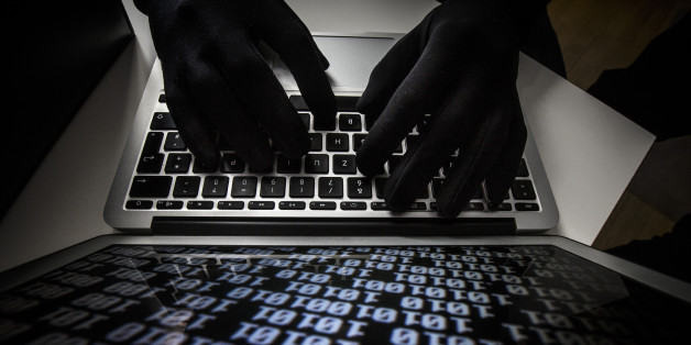 BERLIN, GERMANY - OCTOBER 22: Symbolic feature with topic online crime, data theft and piracy, here a close-up of a keyboard of a laptop with hands in black gloves, on October 22, 2013 in Berlin, Germany. (Photo by Thomas Imo/Photothek via Getty Images)