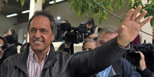 Le favori à l'élection présidentielle argentine Daniel Scioli salue ses partisans après avoir voté