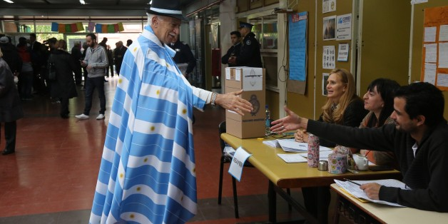 BUENOS AIRES, ARGENTINA - OCTOBER 25: A man wearing Argentina flags greets returning officers before he casts his ballot at a polling station during the presidential elections in Buenos Aires, Argentina on October 25, 2015. (Photo by Omer Musa Targal/Anadolu Agency/Getty Images)