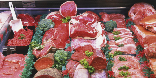 Red meats with herb garnish on display at meat counter