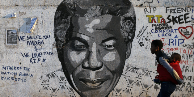 A woman carrying a child on her back walks past a mural showing former South African president Nelson Mandela's face at Katlehong township, 35 km east of Johannesburg, South Africa, Saturday, July 18, 2015.  On Mandela Day, people around the world are encouraged to spend at least 67 minutes doing something positive for their communities in honor of the 67 years that the late South African president Nelson Mandela spent fighting for social justice and a free, democratic country. (AP Photo/Themba