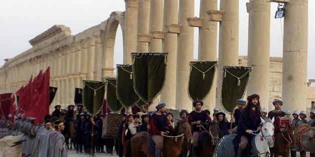 FILE - In this Sept. 27, 2002, file photo, a symbolic trade caravan representing the prosperous trade during the era of Queen Zanobya 260-273AD attend a show held in the ancient city of Palmyra, some 240 kilometers (150 miles) northeast of Damascus, Syria. Islamic State militants beheaded 81-year-old Khaled al-Asaad, a leading Syrian antiquities scholar who spent most of his life looking after the ancient ruins of Palmyra, then hung his body from a pole in a main square of the historic town, Syr