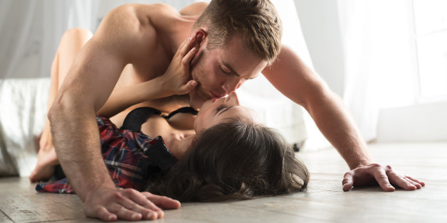 Young couple kissing lovers lounging on the floor. A guy with a naked torso is deposed girl and kisses her on the lips. The girl tenderly embraces his face in his hands both hands.