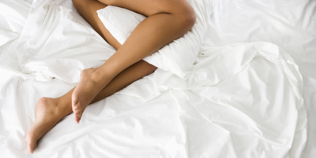 Above view of woman' || chr(39) || 's bare legs holding pillow between knees lying on bed with white sheets.