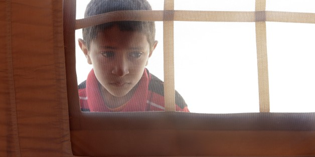 A Libyan child peers into the window of a tent in the U.A.E. Red Crescent refugee camp at the Tunisian village of Dhuheiba, Friday, April 22, 2011. In recent weeks, more than 10,000 Libyans from the border region had crossed into Tunisia, and 1,200 found shelter in a tent camp near the village of Dhuheiba, a few miles from the border. (AP Photo/Pier Paolo Cito)