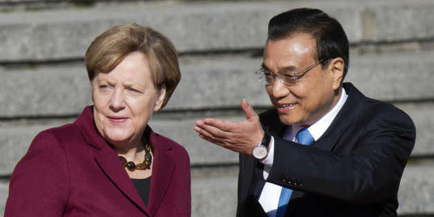 Chinese Premier Li Keqiang, right, shows the way for German Chancellor Angela Merkel during a welcome ceremony held outside the Great Hall of the People in Beijing, China, Thursday, Oct. 29, 2015. (AP Photo/Ng Han Guan)