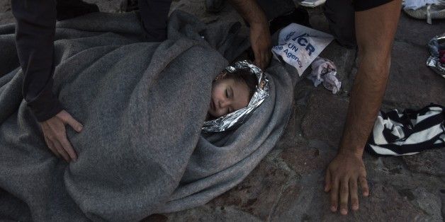 Paramedics and doctors care for a baby girl after a boat with refugees and migrants sunk while was crossing the Aegean sea from Turkey to the Greek island of Lesbos on Wednesday, Oct. 28, 2015. The condition of the child is not known. A 7-year-old boy died off Lesbos, where most migrants land, while a 12-month-old girl was in critical condition in hospital from the same boat accident. Greek authorities said Wednesday that at least five people, including four children, have drowned as thousands o