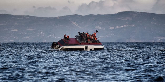 Refugees and migrants call for help as their boat is ready to sink off the Greek island of Lesbos island while crossing the Aegean sea from Turkey on October 30, 2015. More than half a million people have arrived by sea in Greece this year seeking safety and a better life in Europe, while more than 3,200 people have died making the perilous crossing from Turkey. AFP PHOTO / ARIS MESSINIS        (Photo credit should read ARIS MESSINIS/AFP/Getty Images)