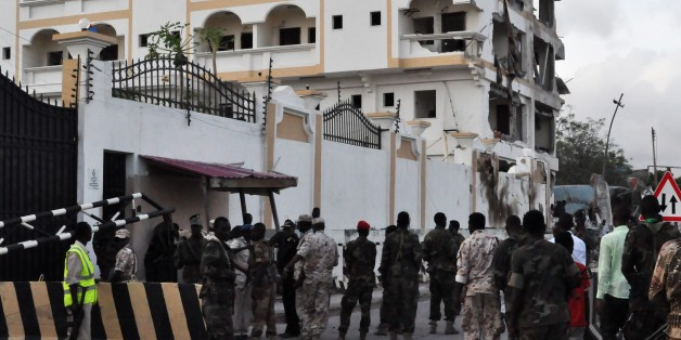 Somali soldiers stand in front of the damaged Jazeera Palace hotel following a suicide attack in Mogadishu on July 26, 2015. Somalia's Shebab insurgents killed at least six people today when they detonated a huge car bomb at a heavily guarded hotel in the capital Mogadishu housing diplomatic missions, officials and witnesses said.  AFP PHOTO / STRINGER        (Photo credit should read -/AFP/Getty Images)