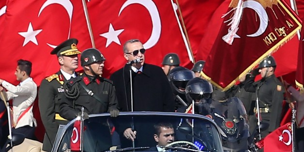 Turkish President Recep Tayyip Erdogan (R) speaks through a microphone next to Chief of the General Staff of the Turkish Armed Forces Hulusi Akar (L) as they are driven in a car past Turkish soldiers during a ceremony marking the 92nd anniversary of Republic Day on October 29, 2015 at the Ataturk Cultural Center in Ankara. AFP PHOTO / ADEM ALTAN        (Photo credit should read ADEM ALTAN/AFP/Getty Images)