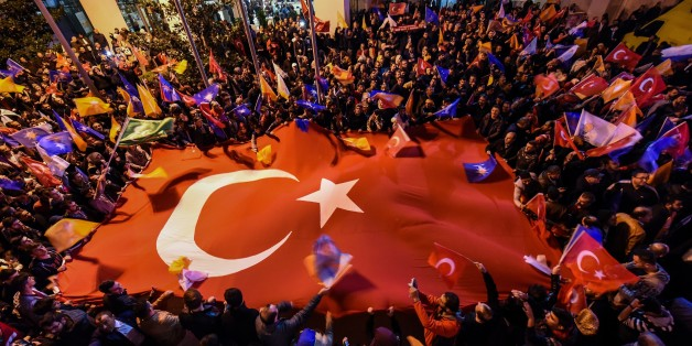 Supporters of Turkey's Justice and Development Party (AKP) hold a giant Turkish flag as they celebrate in Istanbul after the first results in the country's general election on November 1, 2015. Turkey's long-dominant Justice and Development Party (AKP) scored a stunning electoral comeback, regaining its parliamentary majority in a poll seen as crucial for the future of the troubled country. AFP PHOTO / OZAN KOSE        (Photo credit should read OZAN KOSE/AFP/Getty Images)