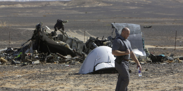 A Russian investigator walks near wreckage a day after a passenger jet bound for St. Petersburg, Russia, crashed in Hassana, Egypt, on Sunday, Nov. 1, 2015. The Metrojet plane, bound for St. Petersburg in Russia, crashed 23 minutes after it took off from Egypt's Red Sea resort of Sharm el-Sheikh on Saturday morning. The 224 people on board, all Russian except for four Ukrainians and one Belarusian, died. (AP Photo/Amr Nabil)