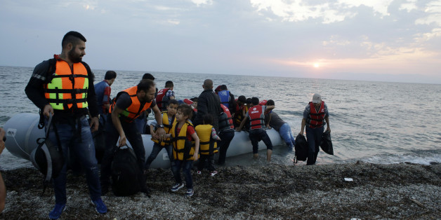 Syrian migrants arrive with an overcrowded dinghy from Turkish coasts at a Mytilene beach, on the northeastern Greek island of Lesvos, early Thursday, June 18, 2015. Around 100,000 migrants have entered Europe so far this year, with some 2,000 dead or missing during their perilous quest to reach the continent. Italy and Greece have borne the brunt of the surge, with many more migrants expected to arrive from June through to September. (AP Photo/Thanassis Stavrakis)