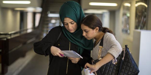 Zwei junge Frauen blicken auf die Resultate ihres Tests im Schulhaus