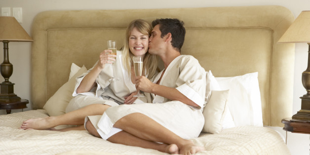 Young Couple Enjoying Champagne In Bedroom