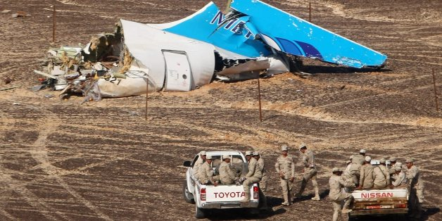 In this photo made available Monday, Nov. 2, 2015, and provided by Russian Emergency Situations Ministry, Egyptian Military on cars approach a plane's tail at the wreckage of a passenger jet bound for St. Petersburg in Russia that crashed in Hassana, Egypt, on Sunday, Nov. 1, 2015. The Russian cargo plane on Monday brought the first bodies of Russian victims killed in a plane crash in Egypt home to St. Petersburg, a city awash in grief for its missing residents. (Maxim Grigoriev/Russian Ministry