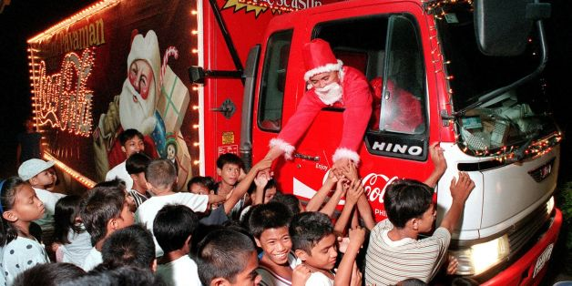 BACOLOD, PHILIPPINES - DECEMBER 4:  A local Coca Cola salesman dressed as Santa Claus riding a specially decorated delivery truck visits an orphanage in Bacolod city in central Philippines, 04 December 1999, where he distributed gifts to the ophans bringing cheers in the spirit of the Christmas season.  (Photo credit should read MARCIAL ANGELO/AFP/Getty Images)