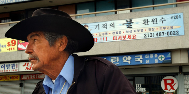 Guadalupe Saldivar, who is unemployed and lives with friends, sits in front of a strip mall with Korean writing on it in the Koreatown section of Los Angeles, Saturday, April 23, 2005. Koreatown is enjoying a renaissance 13 years after riots destroyed many of its businesses, but beneath the facelift an increasing economic divide could threaten its stability, activists said Saturday. (AP Photo/Ann Johansson)