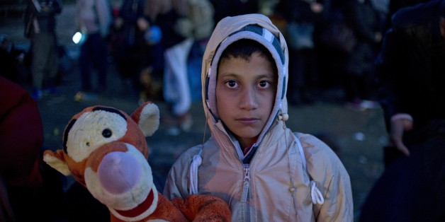 A young boy poses with a soft toy as migrants and asylum seekers wait to enter a registration camp near Gevgelija on October 26, 2015. The EU pledged to help set up 100,000 places in reception centres along the migrant route through the Balkans, in a bid to defuse rising tensions on its eastern frontier over how to deal with the crisis.  AFP PHOTO / NIKOLAY DOYCHINOV        (Photo credit should read NIKOLAY DOYCHINOV/AFP/Getty Images)