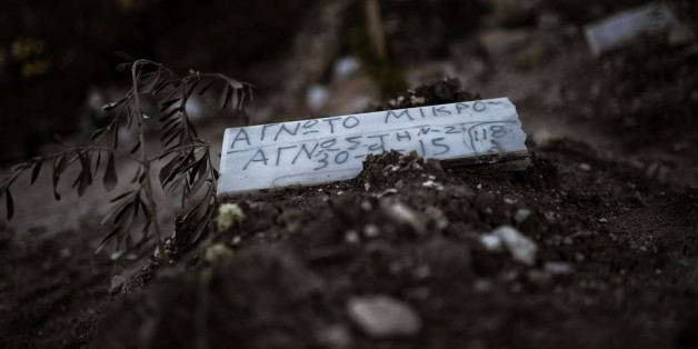 TO GO WITH AFP STORY BY MARINA RAFENBERG A piece of marble reading 'Unidentified child' is placed over the grave of a child who drowned on its way from Turkey to the Greek island of Lesbos, at a makeshift cemetery in Mytilene, on the island of Lesbos, on November 4, 2015. AFP PHOTO / ARIS MESSINIS        (Photo credit should read ARIS MESSINIS/AFP/Getty Images)