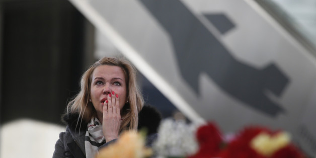 A woman reacts at an entrance of Pulkovo airport during a day of national mourning for the victims of the plane crash, outside St. Petersburg, Russia, Tuesday, Nov. 3, 2015. In a massive outpouring of grief, thousands of people flocked to St. Petersburg's airport, laying flowers, soft toys and paper planes next to the pictures of the victims of the crash of a passenger jet in Egypt that killed all 224 on board in Russia's deadliest air crash to date. (AP Photo/Dmitry Lovetsky)