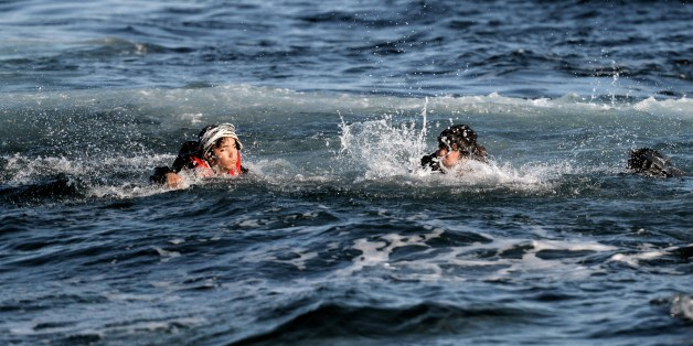 Refugees and migrants swim as they try to reach the shore of the Greek Lesbos island after crossing the Aegean Sea from Turkey on November 2, 2015. More than 218,000 migrants and refugees crossed the Mediterranean to Europe in October -- a monthly record and more than during the whole of 2014, the United Nations said Monday. AFP PHOTO / ARIS MESSINIS        (Photo credit should read ARIS MESSINIS/AFP/Getty Images)