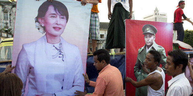 Supporters of Myanmar opposition leader Aung San Suu Kyi's National League for Democracy party place posters of her and her father Aung San at an event to celebrate the final day of campaigning in Yangon, Myanmar, Thursday, Nov. 5, 2015. On Sunday Myanmar will hold what is being viewed as the country's best chance for a free and credible election in a quarter of a century. (AP Photo/Mark Baker)