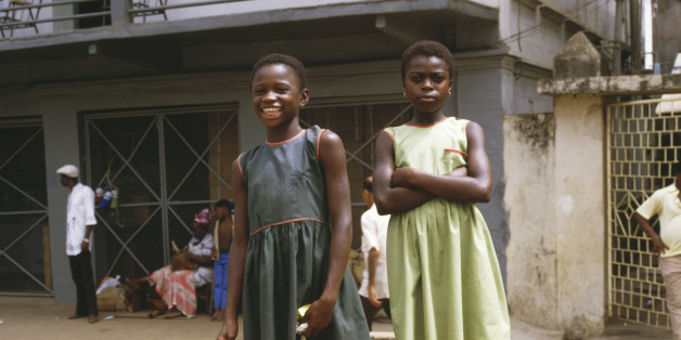 Two young girls pose for the camera along Fourah Bay Road in Freetown, Sierra Leone, March 1985 (Photo by Frances M. Ginter/Getty Images)