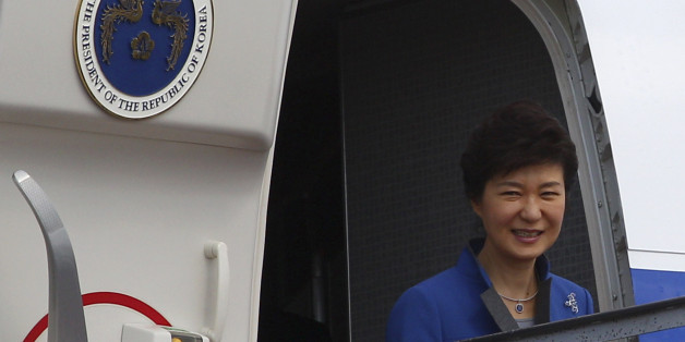 South Korean President Park Geun-hye smiles from her plane upon arrival at Bali airport, Indonesia, Sunday, Oct. 6, 2013 to attend the Asia-Pacific Economic Cooperation (APEC) forum. (AP Photo/Firdia Lisnawati)